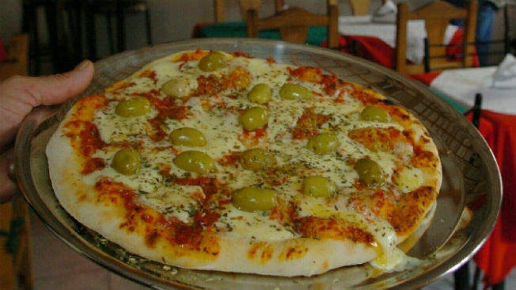Tomasino ofrece sus pizzas para compartir con amigos.